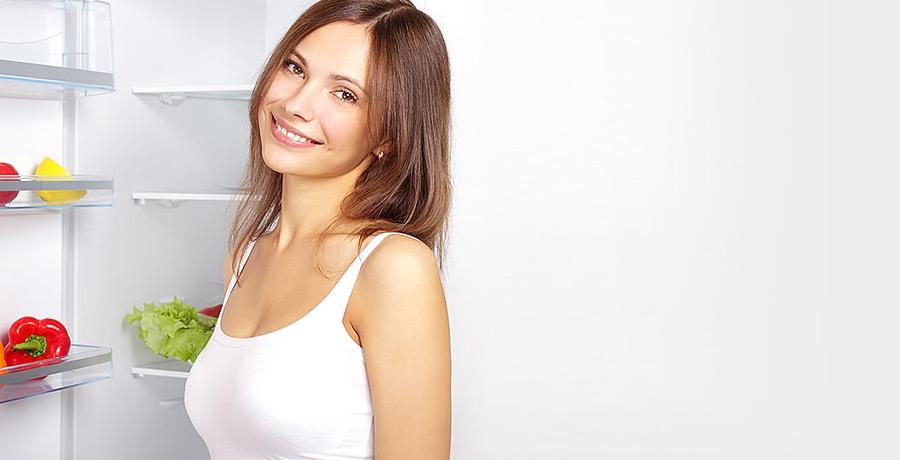 Frau steht vor Kühlschrank und lächelt