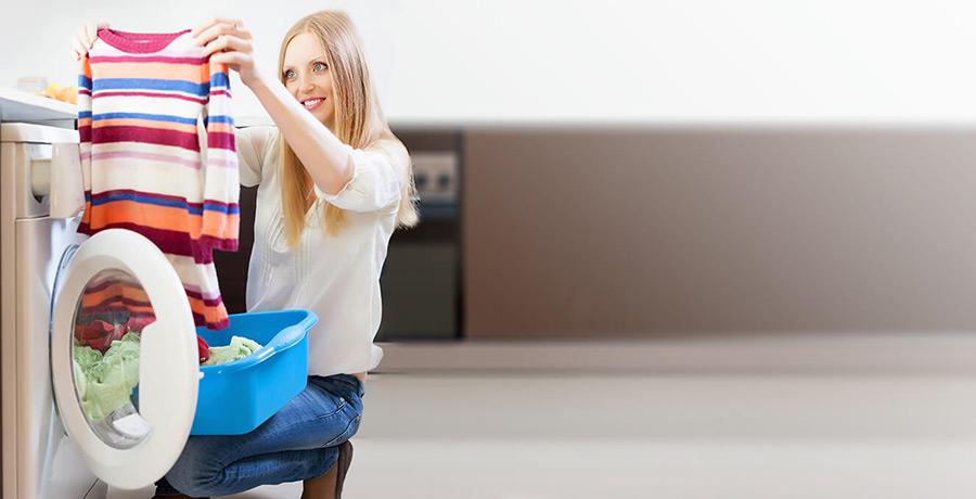 Frau nimmt Wäsche aus Waschmaschine
